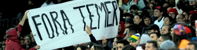 Fans at a football match hold a banner that reads Fora Temer - Portuguese for Temer Out