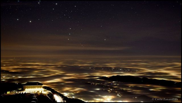Orion rising over lights and fog in the province of Treviso in north east Italy