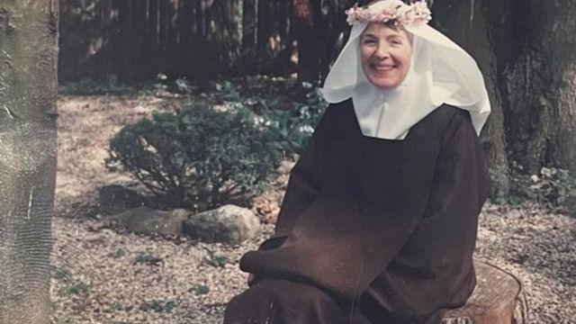 Irmã Mary Joseph em seu hábito de freira com uma coroa de flores