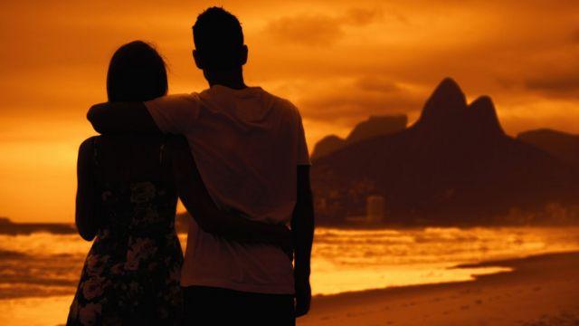 Pareja mira el atardecer en Rio de Janeiro.