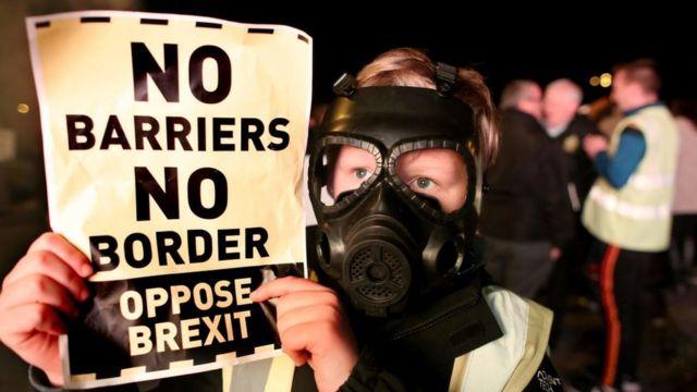 Manifestante anti-Brexit com máscara de gás segura uma placa que diz: 'sem barreiras, sem fronteiras'