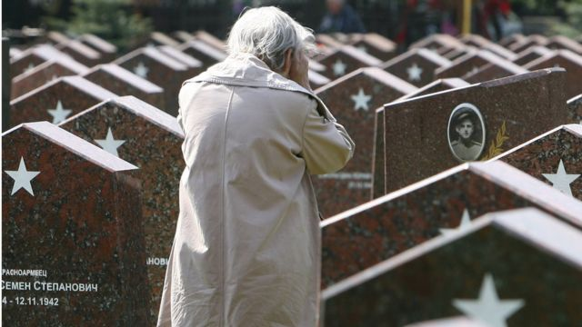 An elderly Russian woman cries while visiting a military cemetary in Moscow where numerous veterans of WWII are buried