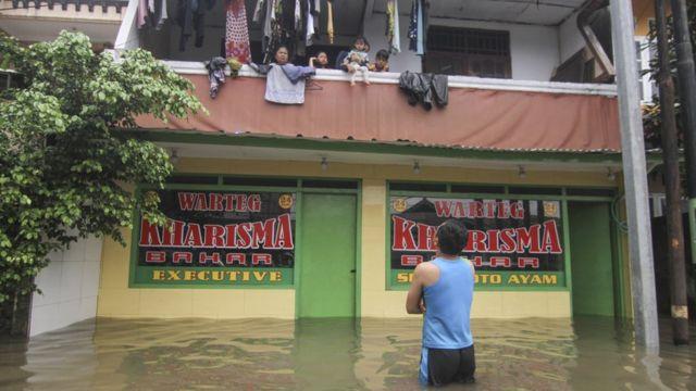 Sejumlah warga mengungsi di lantai dua rumahnya saat banjir di kawasan Kampung Makasar, Jakarta Timur, Selasa (25/02).