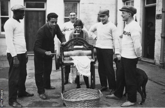 31 décembre 1926: Len Johnson, champion britannique de boxe poids lourd, aide à la mutilation, son père est à gauche. (Photo par Brooke / Agence de presse d'actualité / Getty Images)