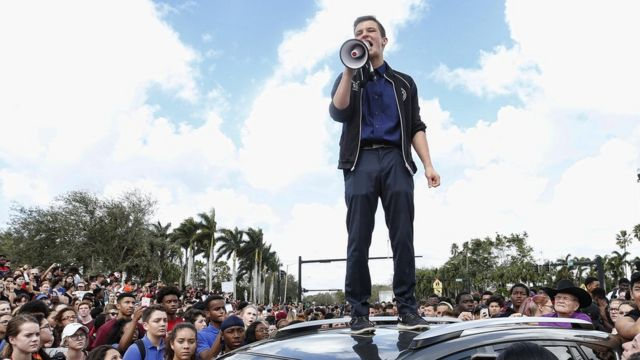 Кэмерон Кэски стоит на крыше автомобиля