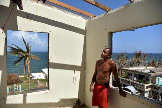 Un joven mira su casa destruida por el huracán.