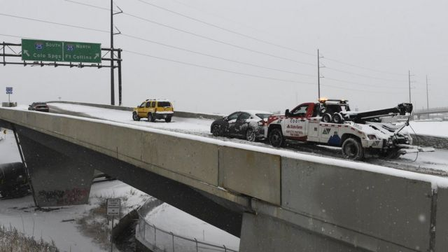 A tow truck pushes a car up the ramp in Denver