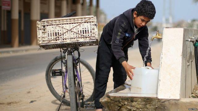 Un niño llena una garrafa de agua en una fuente
