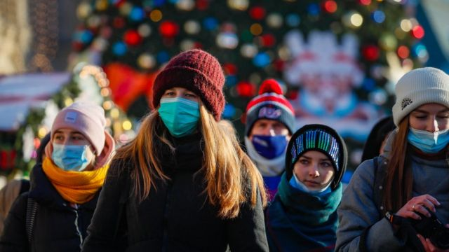 "Russian people wearing a protective face masks walk on a street decorated for the upcoming Christmas and New Year""s celebrations during the pandemic of SARS-CoV-2 coronavirus Moscow, Russia, 28 December 2020"