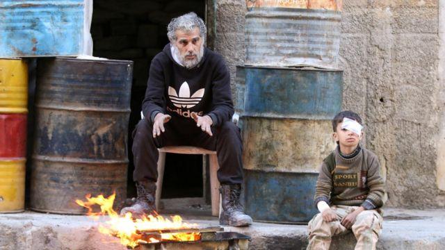 طفل سوري يجلس بجانب رجل يتدفأ بالنار في شرقي حلب