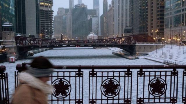 Imagem mostra mulher caminhando em meio a prédios e à área congelada em Chicago, em meio a intensa onda de frio nos EUA
