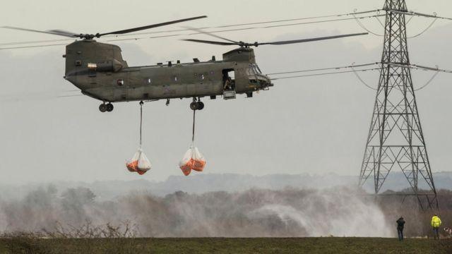 暴風雨「フランク」の接近に備え、ランカシャー・クロストンの村に土嚢を運ぶ英空軍ヘリ