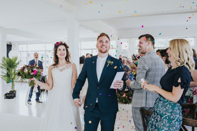 Married couple walk down the aisle as colourful confetti is thrown