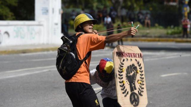 Un manifestante ataca a las fuerzas antidisturbios.