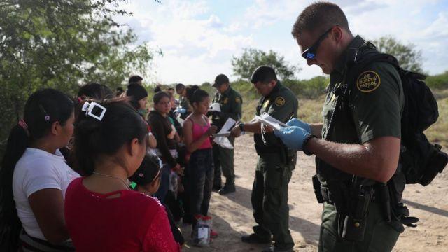 Inmigrantes junto a oficiales de frontera de Estados Unidos.