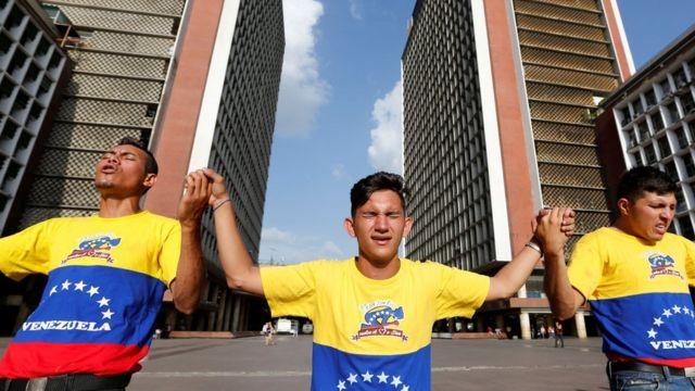 Tres personas rezan frente a la sede del CNE