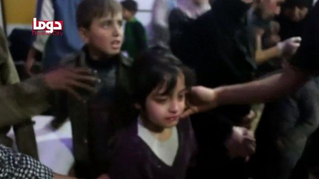 Children are given medical checks in what is said to be the rebel-held Syrian town of Douma, 7 April