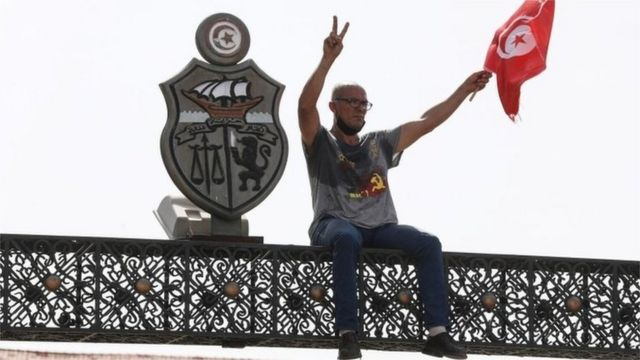 متظاهر على بوابة خارج البرلمان التونسي