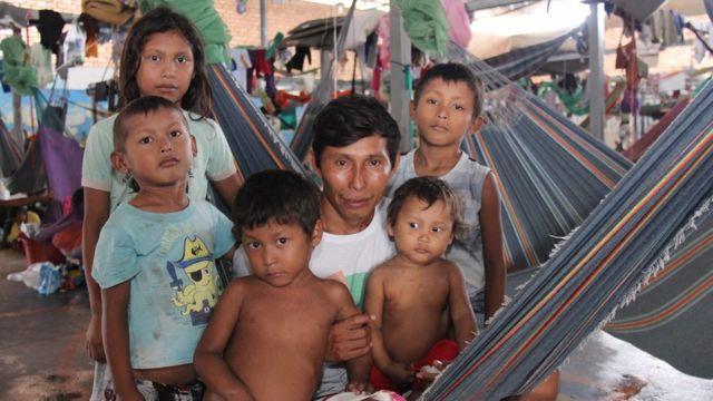 Indígena venezuelano Eulirio Baes sentado numa rede, cercado de cinco crianças de diferentes idades