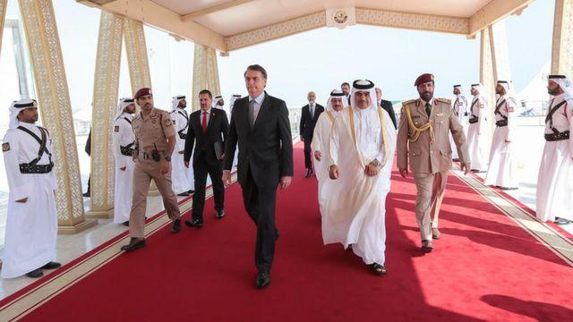 Bolsonaro caminha sobre tapete vermelho em área coberta, rodeado por autoridades e militares do Catar