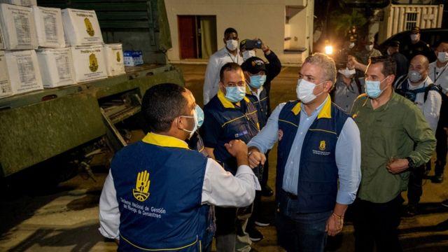 El presidente de Colombia, Iván Duque, saluda a los trabajadores del reparto de ayuda