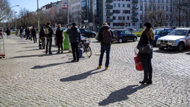 Organik bir markette alışveriş yapmak için 1,5 metre arayla sıraya giren Berlinliler