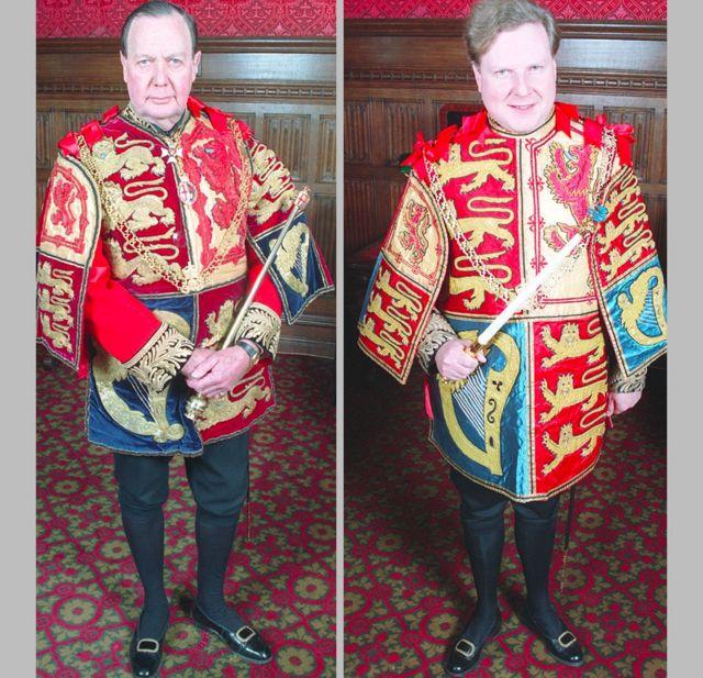 تم تصوير الراحل السير كونراد سوان (يسار) في عام 1994 على أنه غارتر ملك الأسلحة في لوحة احتفالية وهو يحمل العصا الخاصة به وتوماس وودكوك (على اليمين) الذي كان آنذاك سومرست هيرالد وهو الآن غارتر ملك الأسلحة