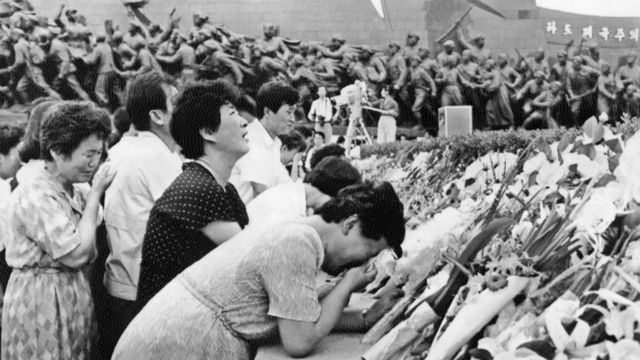 People cry after putting flowers in front of the statue of North Korean President Kim Il Sung to mourn the death of the president in Pyongyang, on July 09, 1994.