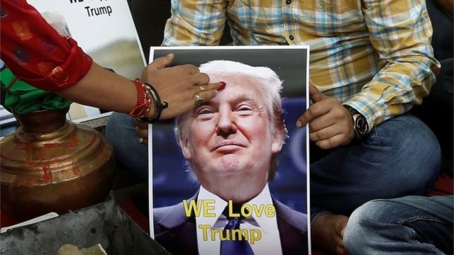 """A priest applies a """"tika"""" on the portrait of Republican U.S. presidential candidate Donald Trump, during a special prayer organised by Hindu Sena, a Hindu right-wing group, to ensure his victory in the upcoming elections"""