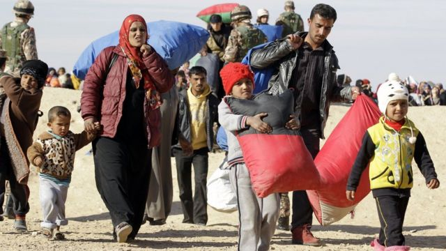 A Syrian refugee family walk with their belongings after crossing into Jordan, near the town of Ruwaished, east of the Jordanian capital Amman, on January 14, 2016.