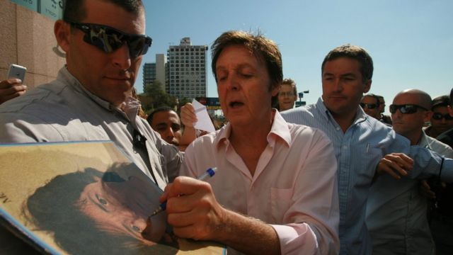 El cantante Paul McCartney firma autógrafos.
