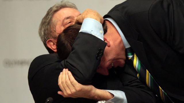 Sentado, Lula abraça Eduardo Paes, que se abaixa em direção do ex-presidente - ambos rindo em ambiente fechado