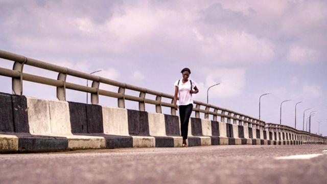 A woman walking on the Third Mainland Bridge in Lagos, Nigeria