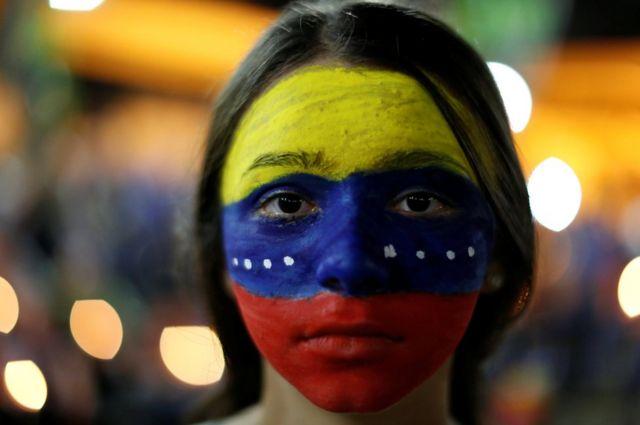 Manifestante con los colores venezolanos pintados en la cara