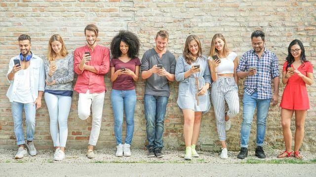 Grupo de jóvenes mirando a su celular.