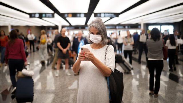 Mujer con mascarilla en el aeropuerto argentino de Ezeiza