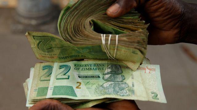Un vendeur à Harare avec d'anciens billets de 2 dollars et de nouveaux billets de 2 dollars zimbabwéens en novembre - Zimbabwe