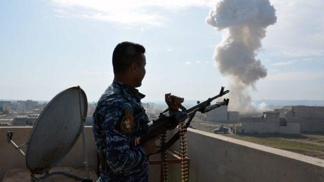 عسكري من القوات العراقية يراقب تدمير سيارة مفخخة تركها مقاتلوا التنظيم في منطقة سيطرت عليها القوات العراقية جنوب شرق الموصل