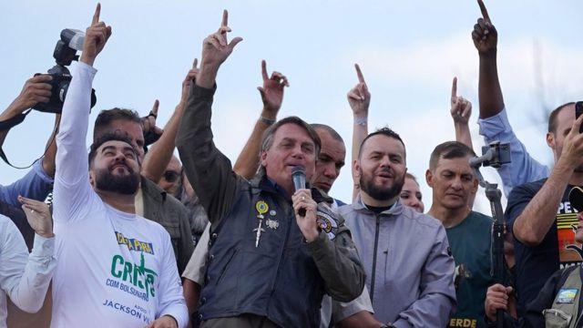 Presidente levante a mão ao lado de apoiadores em palanque