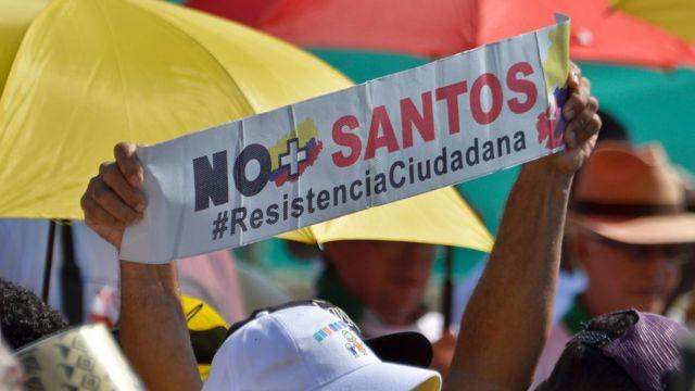 Simpatizantes de la oposición al proceso de paz muestran pancartas con el No