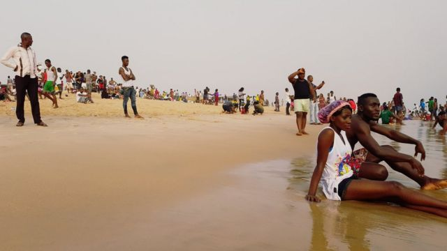 Couple sit down close to di water for beach