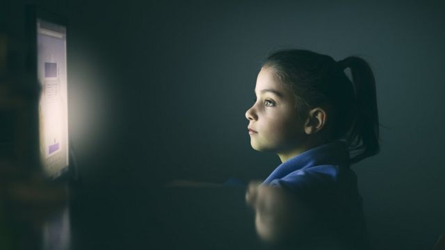 Girl illuminated by the glow of a screen