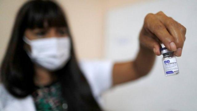Una trabajadora sanitaria muestra la vacuna rusa que se suministra en Argentina.
