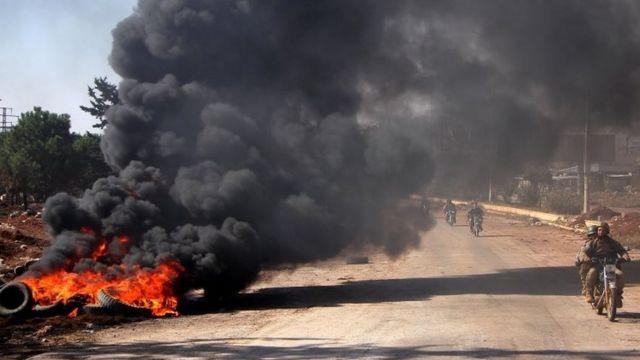 أفراد المعارضة المسلحة يمرون بجانب إطارات مشتعلة في غرب حلب