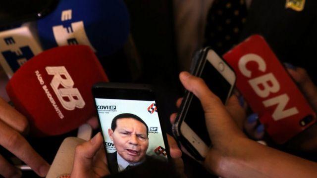 Imagem de Mourão aparece em celular em meio a microfones de diversos veículos de imprensa