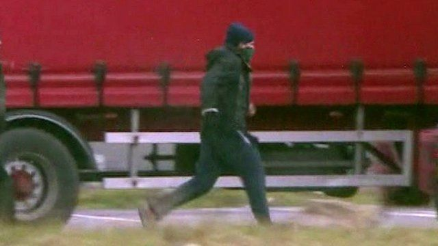 A man with his face covered running to a truck.