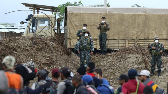 Militares peruanos y migrantes a ambos lados de la frontera.