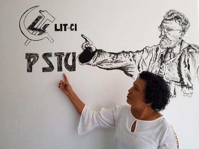 Vera Lúcia Salgado, candidata presidencial do PSTU, em frente a um desenho de Trotsky na sede da legenda