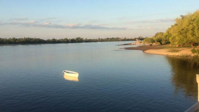 Un bote blanco en una calmada laguna en la que se refleja el cielo, los árboles y el mismo bote