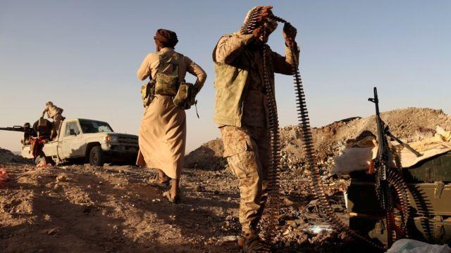 متشدد يمني موال للحكومة يحمل ذخيرة من مدفع رشاش إلى موقع قيادي أثناء قتاله لمسلحي الحوثي في مدينة مأرب اليمنية (16 مارس / آذار 2021).
